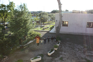 La maestra acompañando a cinco de sus niños hacia el lugar de recogida por los padres.